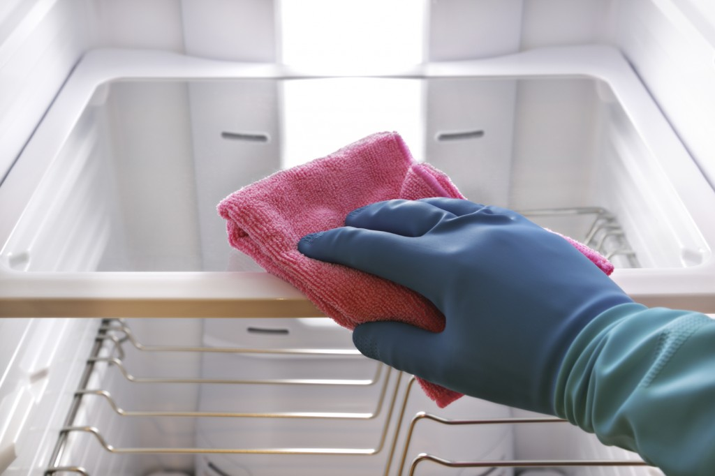 Hand with rubber glove and cloth cleaning refrigerator shelf concept for hygiene